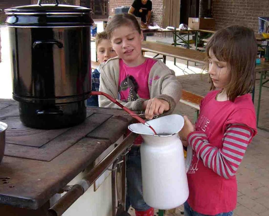 Kinder bereiten auf einer historischen Kochmaschine Marmelade selbst zu. Foto: LWL