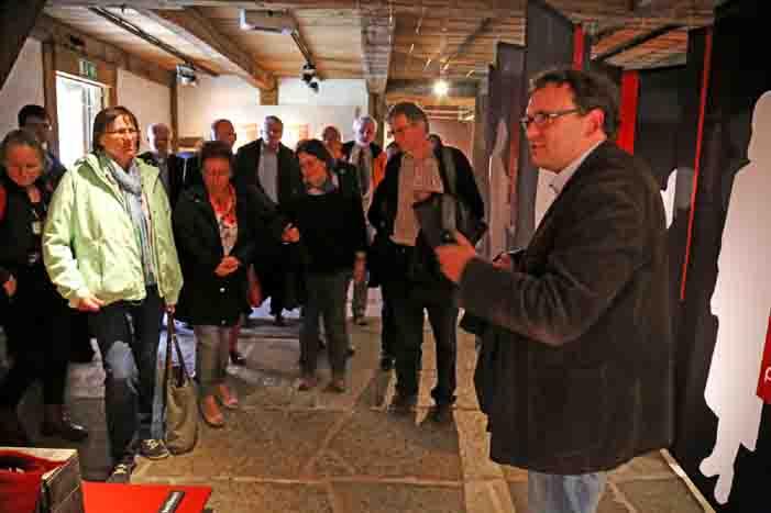 """Ausstellungskurator Hauke-Hendrik Kutscher (rechts) gab den Workshop-Teilnehmern bei einem Rundgang Einblicke in die aktuelle Sonderausstellung """"Geraubte Jahre. Alltag der Zwangsarbeit in Westfalen"""" im LWL-Freilichtmuseum Detmold. Foto: LWl/Jähne"""
